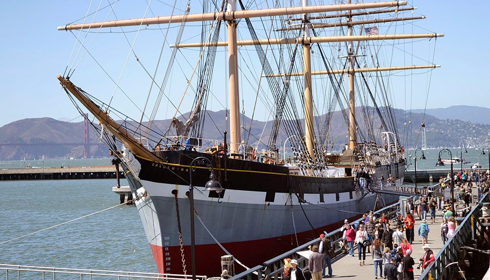 People walk by a three-masted ship docked alongside pier
