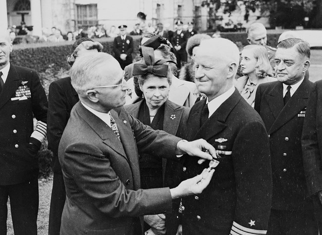 President Truman pins a gold star on Admiral Nimitz amidst a crowd standing outside the White House