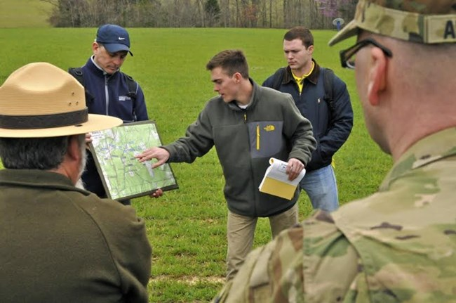 Man points out places on a park map to military staff on a tour.