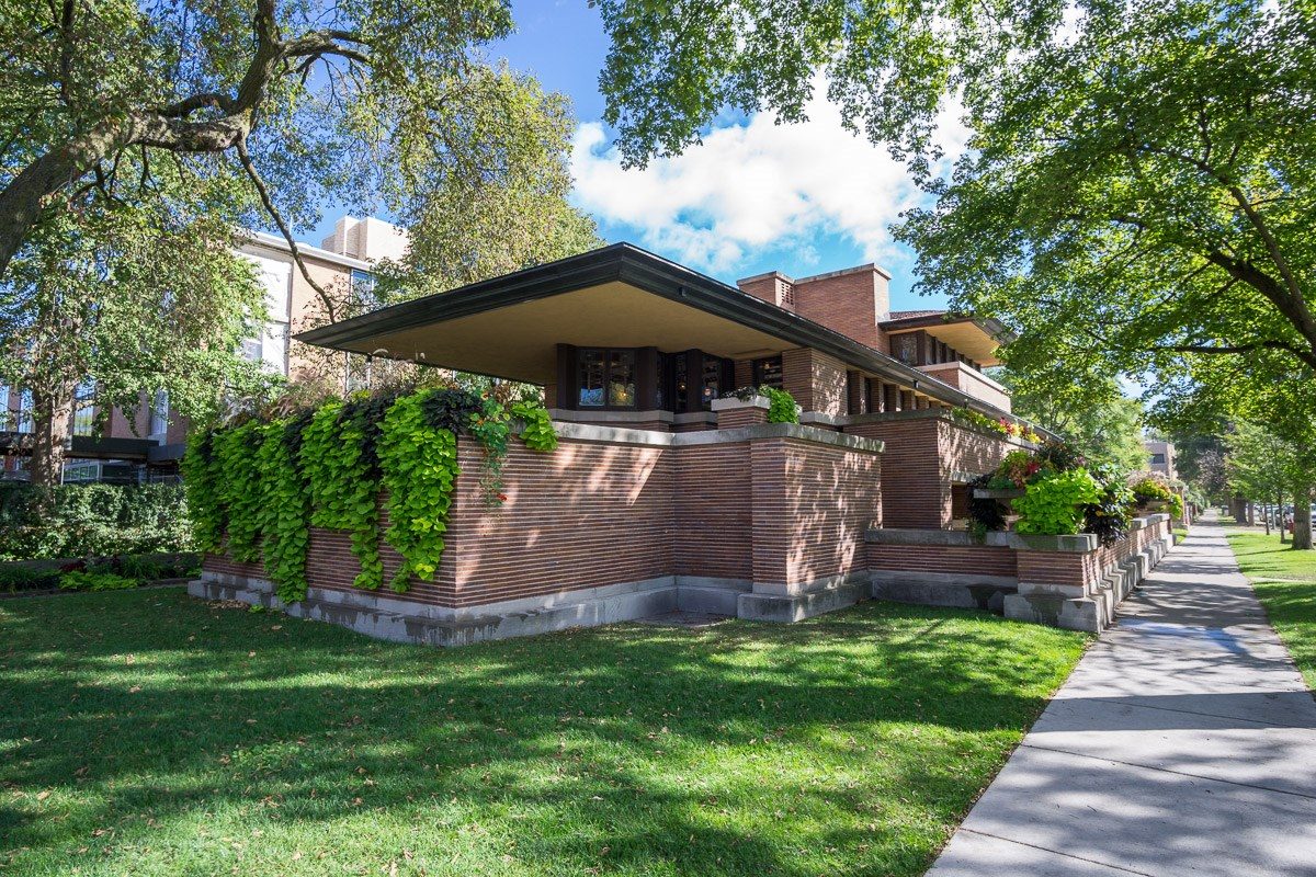 view of Frederick C. Robie House and lawn with neighboring sidewalk