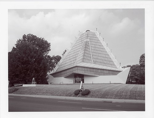 a glazed, pyramidal tower, broad in form and made up of three sides, and a base of reinforced concrete, steel, and glass