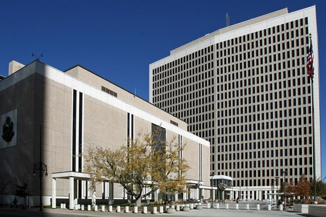 A broad, five-story courthouse set perpendicular to an 18-story office tower, both of which frame an open plaza at the southeastern corner of the property