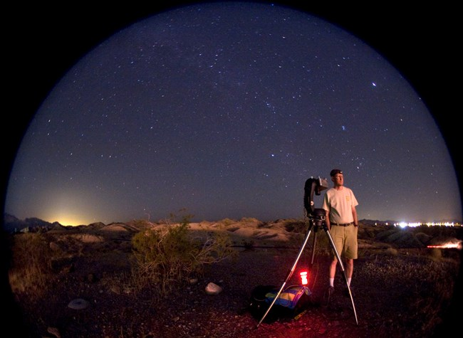 An NPS scientist in the field assesses natural and artificial sources of light