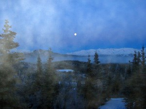 Fog shrouds this view of a rising moon over Healy Ridge in Denali National Park and Preserve.
