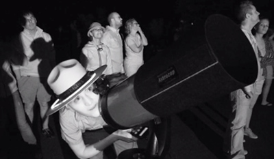 A ranger with Dead Horse State Park looks through a telescope for a view to the night sky.