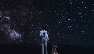 Boy stands with dog under starry night