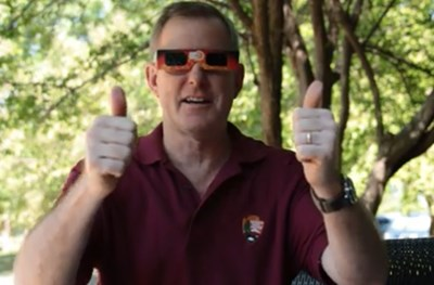 A man wears eclipse sunglasses and gives the thumbs up sign
