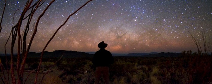 A cowboy contemplates a clear, starry night sky over the desert horizon at Big Bend National Park, Texas.