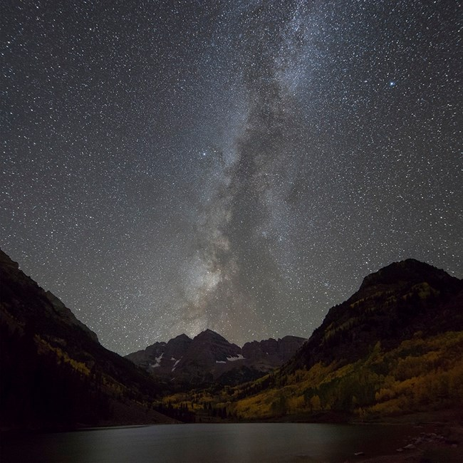 The natural light of the Milky Way and constellations stand out against a dark sky over Maroon Bells, Colorado