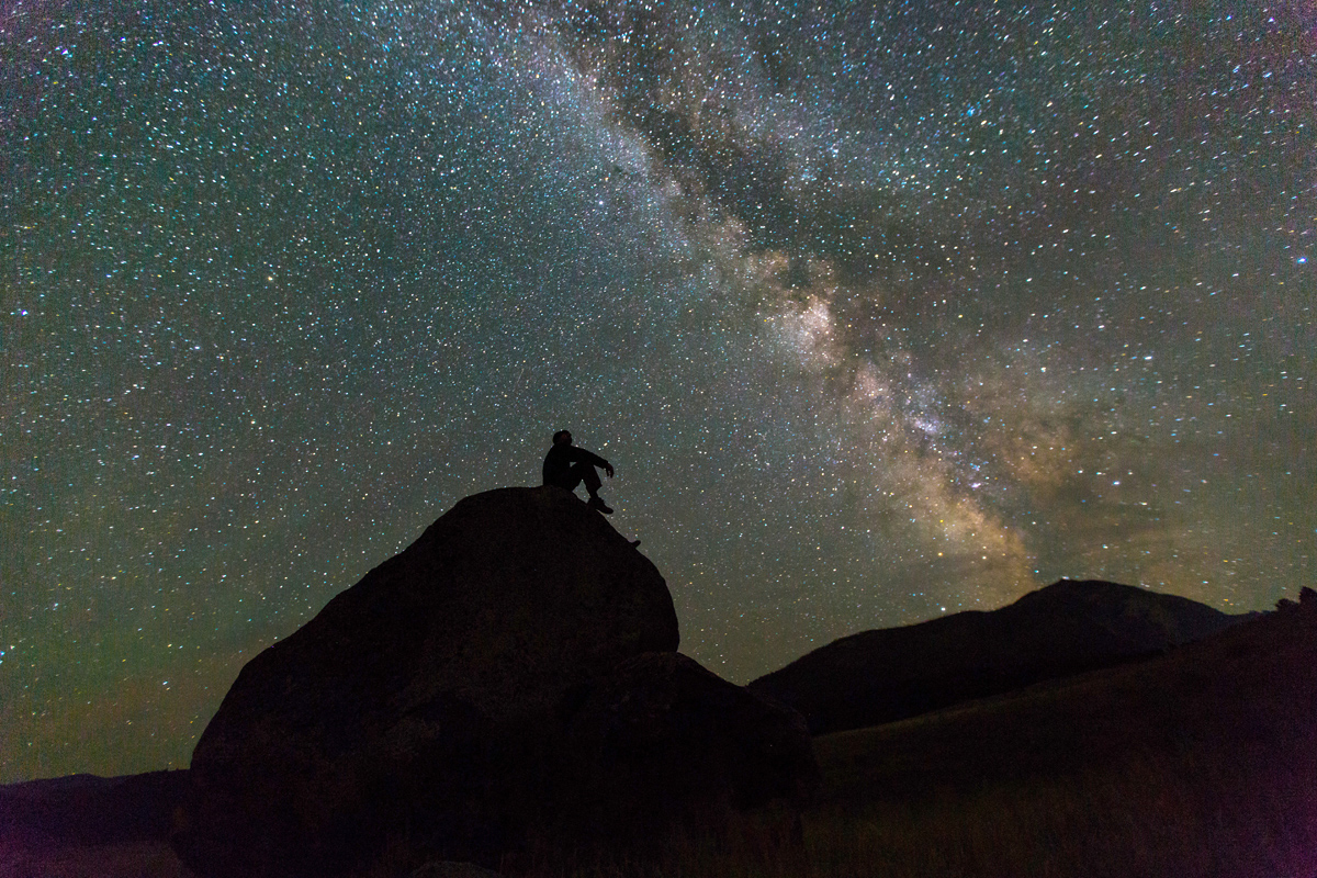 A man shown in silhouette against a brilliant night sky sits in contemplation of the galaxy from his rock perch at Yellowstone National Park.