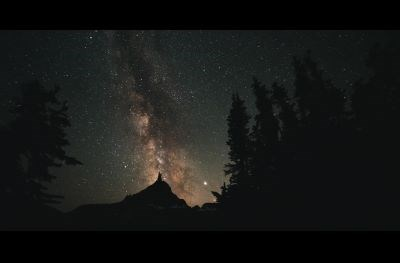 the milky way shines bright over a forested mountain
