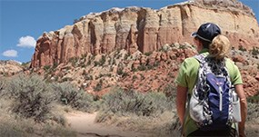 the back of a woman wearing hiking clothes and backpack in foreground with a red and tan rock cliff in the background.