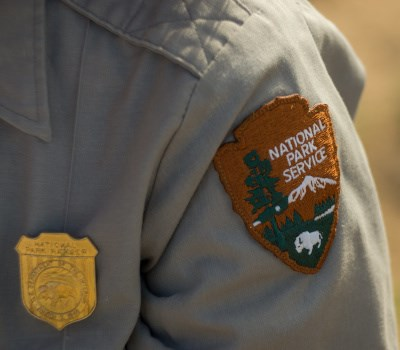 Shoulder of uniformed park employee showing NPS arrowhead and badge