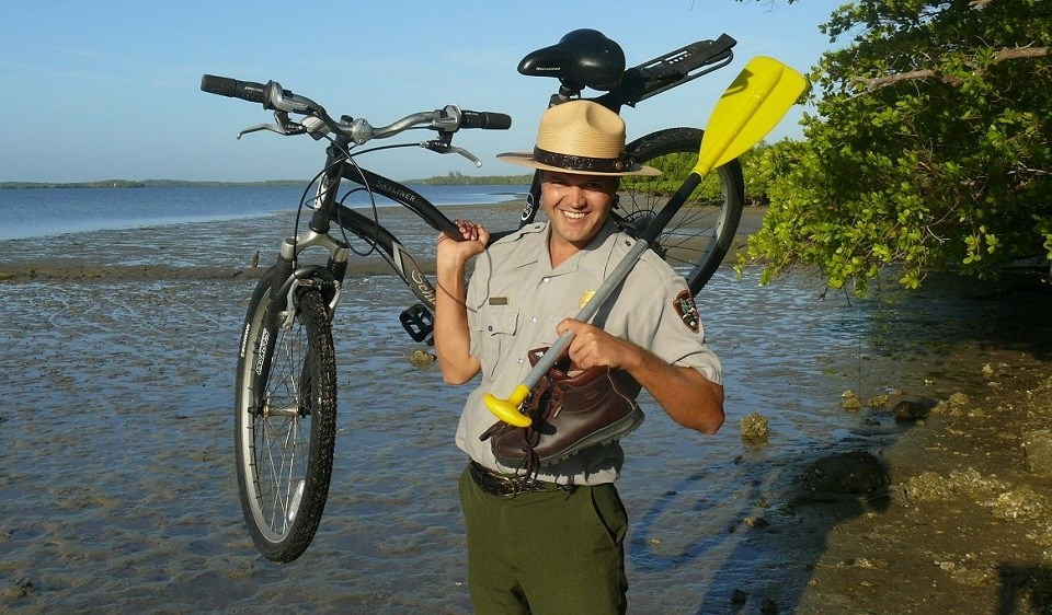 Ranger standing on a shoreline holding a bike, paddle, and hiking boat