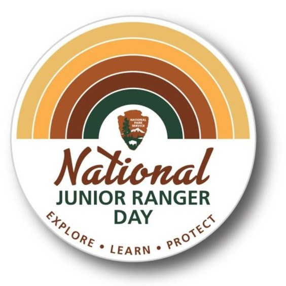 "Button with NPS arrowhead and earth-tone rainbow and text ""National Junior Ranger Day EXPLORE LEARN PROTECT"""