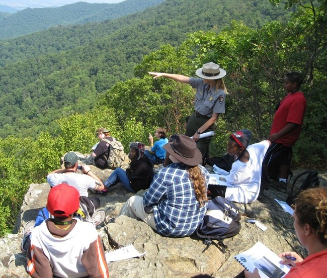 Ranger giving a program to a tour on a rocky outcrop