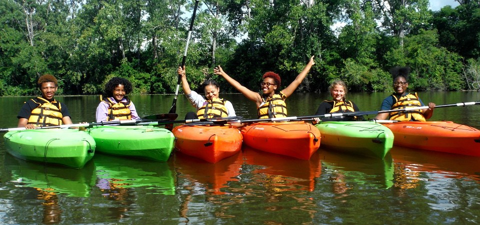 Six girls floating in kayaks and posing for the camera