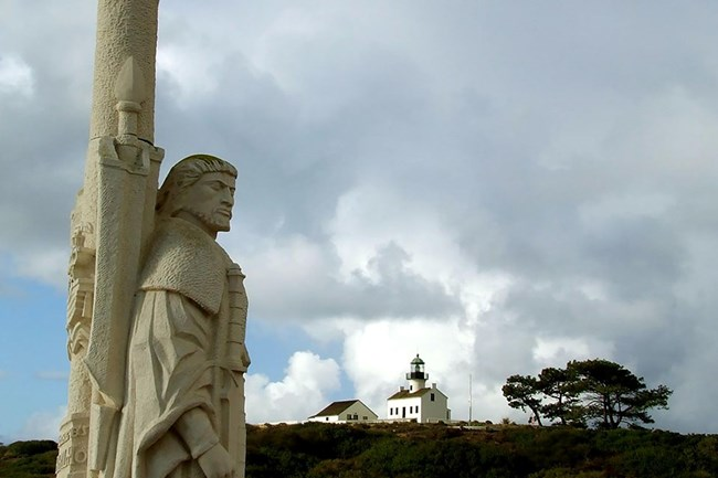 stone monument of Juan Rodriguez Cabrillo with hill and clouds in the background