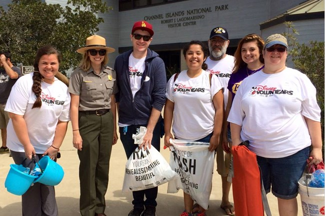 group of people standing with park ranger all holding trash bags