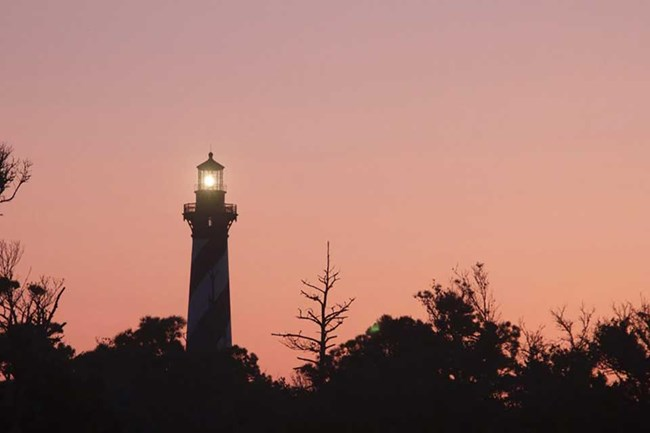lighthouse at sunset with trees in the foreground