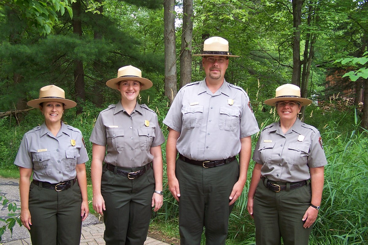 four rangers standing in a forest