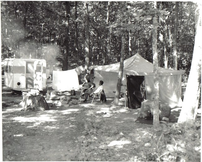 Two campers seated beside a tent and camper vehicle at Lewis Mountain Campground