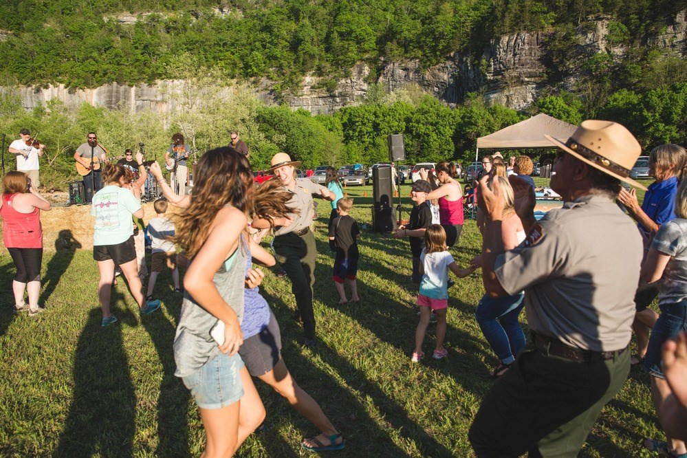 Visitors and park employees dance in the grass in front of a band