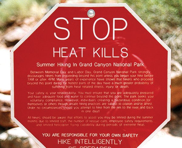 A stop sign with a detailed message about dangers of hiking in hot conditions.