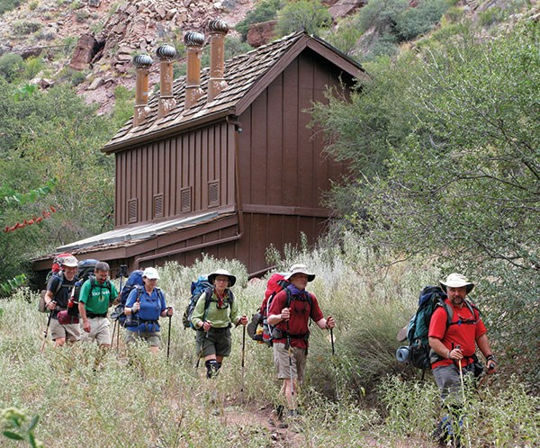 A backpacking party passes the Cottonwood Campground restrooms on the North Kaibab Trail.