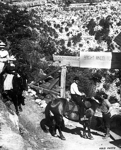 "Riders pay a toll at Cameron's Bright Angel Trailhead around 1910. Gate with toll sign: ""Footman will please stand on trail except when passing animals."" Corner of Kolb studio building on right."