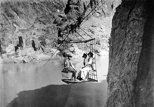 Rust's aerial tramway crosses the Colorado River from south to north around 1908 with two women and one man riding as passengers in a cage.