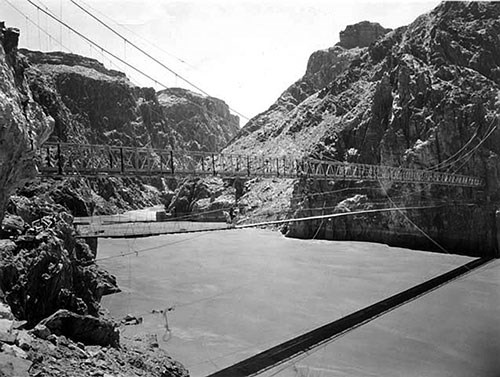 View of the 1921 swinging bridge and the 1928 Kaibab suspension bridge over the Colorado River around 1928, before the original bridge was removed.