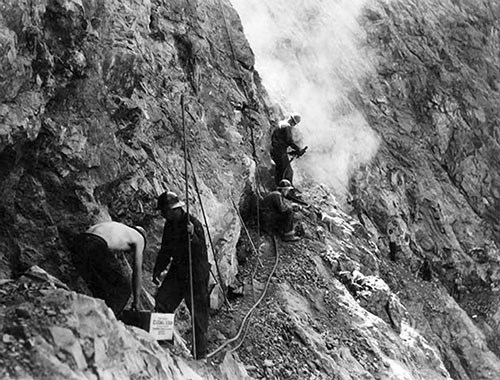 Civilian Conservation Corps enrollees construct a portion of the River Trail along a ledge around 1935.