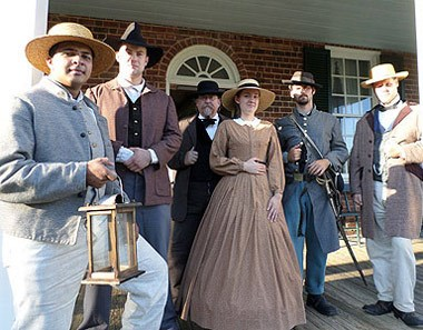 Appommatox 1865 Foundation members posing in period clothing during a living history lantern tour.