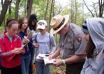 A park ranger and young adults identify species during a BioBlitz species inventory.