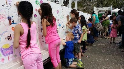 Children draw on the Friendship Mural during the Cherry Blossom Festival.