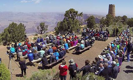Approximately 100 participants attend the re-dedication ceremony of the Desert View Watchtower.   Participants are seated with a view of the Grand Canyon and the Desert View Watchtower.