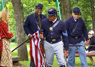 Soldiers in Civil War Period Clothing march with the American Flag and rifles during a living history program at Freedoms Frontier National Heritage Area.