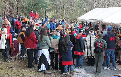 A large group gathers around to witness the  groundbreaking of the Huna Tlingit Tribal House.