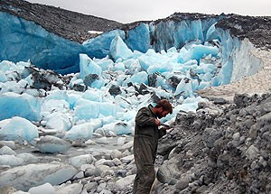 A GeoScientist-in-the-Parks volunteer collects research data in a glacial environment.