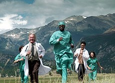 Doctors running in a field against mountain backdrop.