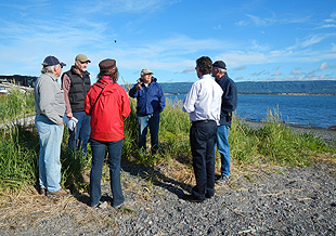 Community members discuss the trail project on the banks of Kachemak Bay.