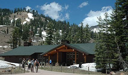 Visitors exiting the Kohm Yah-mah-nee Visitor Center, surrounded by snow spotted mountains.