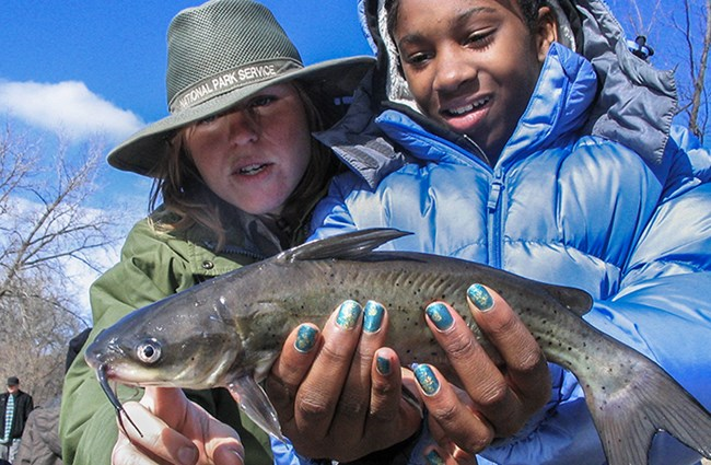 girl holds fish as ranger describes it