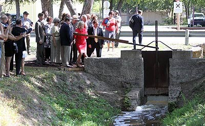 Members of the San Antonio Conservation Society, Senator Kay Bailey Hutchinson, and National Park Service employees lift the gate on the restored San Juan Acequia to allow water to flow.