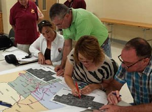 Community members work on maping out features along a future hiking and biking trail.