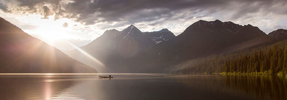 the sun begins to set as a canoe floats on a serene lake surrounded by mountains