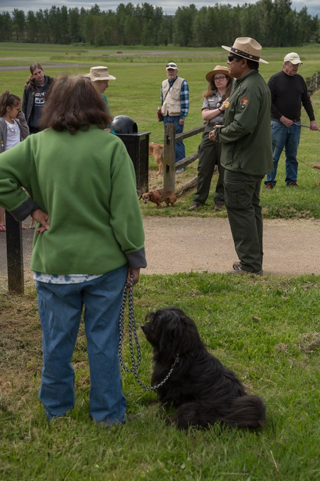 Woman and her dog listen to a park ranger.