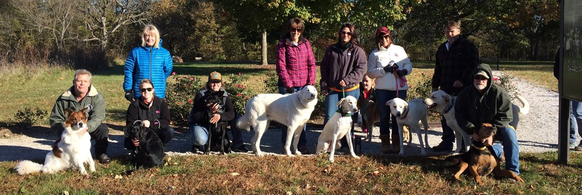 Nine people and their pets pose for a group photo on a fall day.