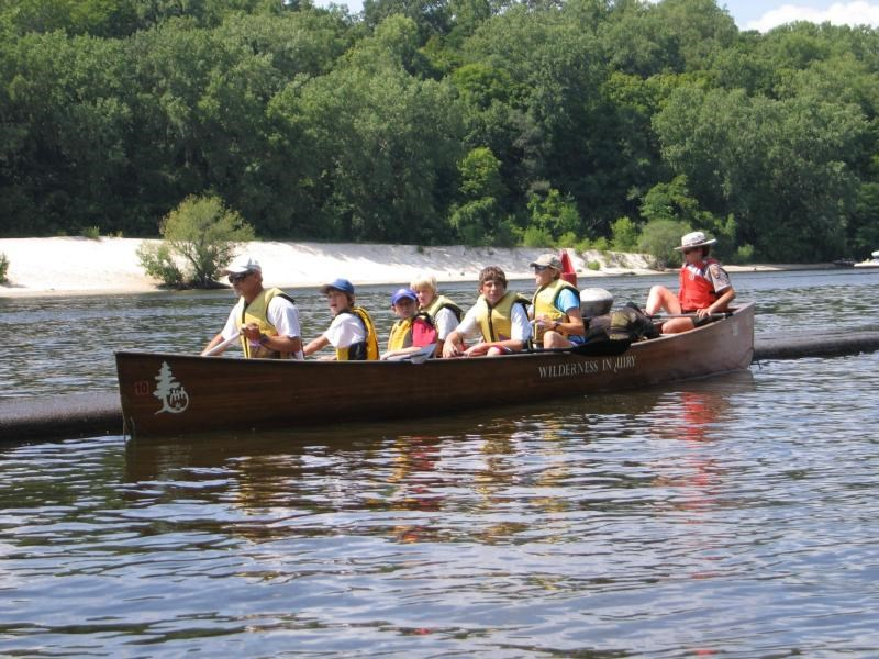 National Park Service Ranger and a group of children paddling in a large canoe.